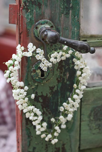 Heart-shaped wreath of lilies of the valley hanging from vintage doorknob with lock.