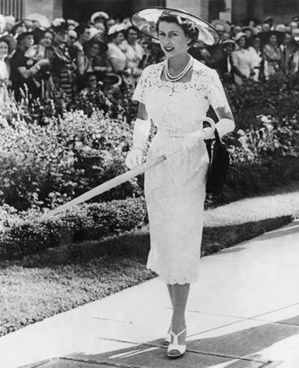 Queen Elizabeth II in hat, gloves, matching shoes, pearls, with umbrella