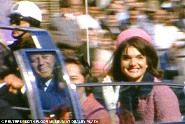 Jacqueline Kennedy in pink suit and pillbox hat, riding with JFK in limo in Dallas on November 22, 1963.