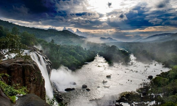 Kerala, India, waterfall and green mountains during monsoon rainy season.