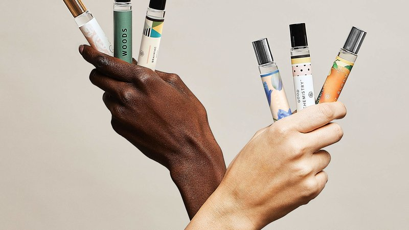 Hands holding rollerballs of Target Good Chemistry fragrance collection