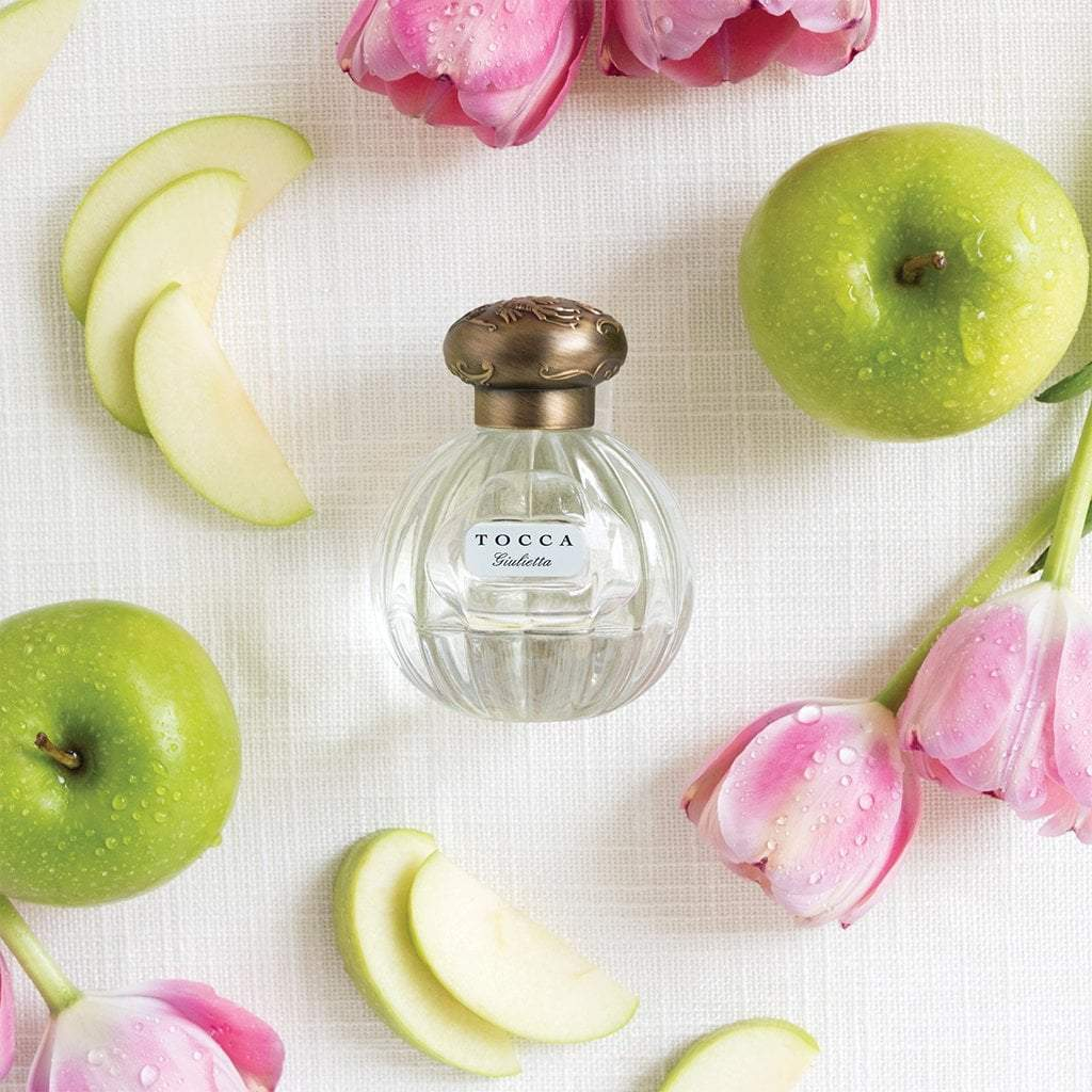 Bottle of Giulietta eau de parfum from Tocca with pink tulips and green apples