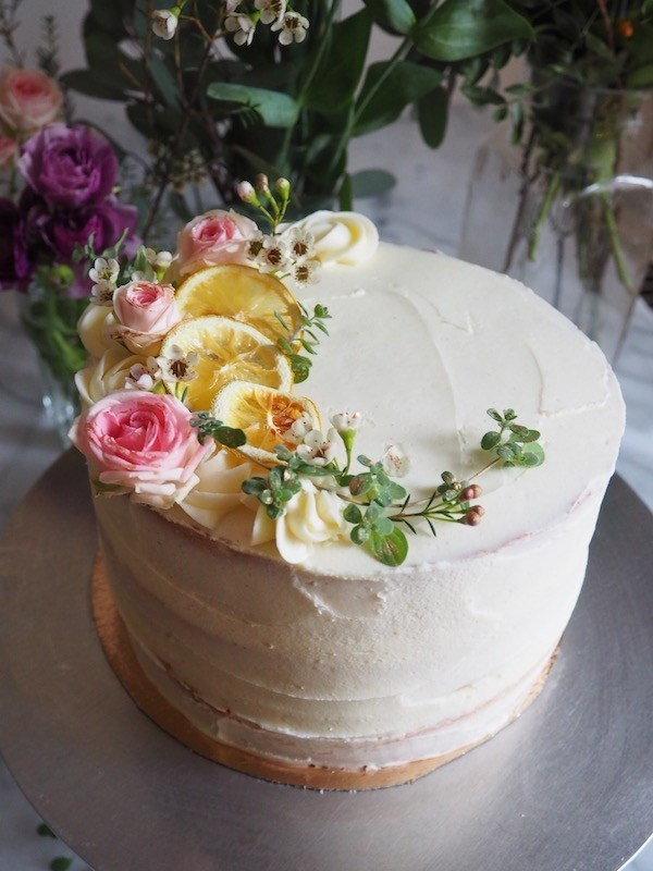 Citrus cake with vanilla icing and flowers, by Molly Wilkinson