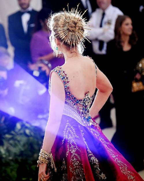 Back of Blake Lively, red and gold embroidered ball gown.