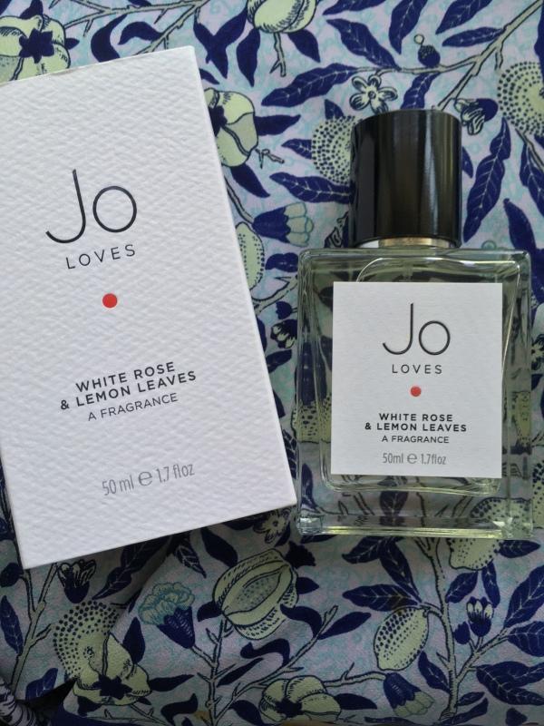 """Bottle of Jo Loves White Roses & Lemon Leaves, against William Morris' """"Fruit"""" fabric design."""