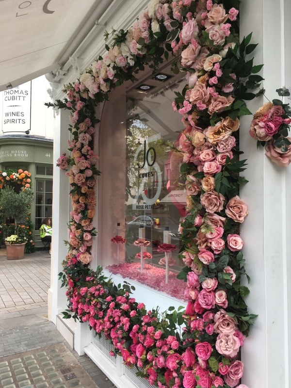 Storefront of Jo Loves fragrance boutique, decorated with roses.