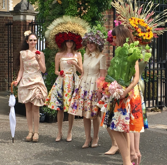 Singers with giant flower hats and flowered dresses at RHS Chelsea Flower Show.