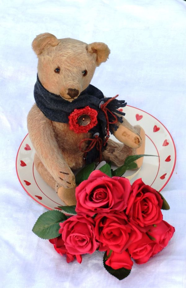 Old teddy bear with red roses
